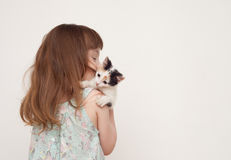Girl standing with her back and holding a kitten Royalty Free Stock Image