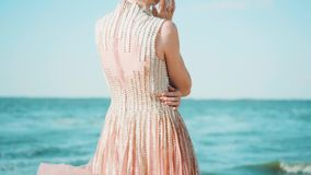 Girl standing with her back to the camera, her blond hair and a light long train of pink shiny dress fluttering in the. Wind, hugging her with one hand, gently stock video