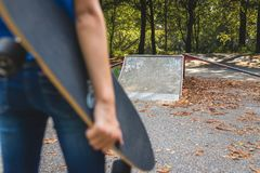 A girl is standing with her skateboard on a skate park in front stock image