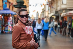 Girl standing and holding a lollipop in the city. Girl standing and holding a red and white lollipop in the city Stock Photos