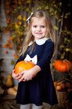 Little girl holding pumpkin in autumn interior stock photography