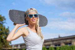 Girl standing and holding skateboard behind her head Royalty Free Stock Images