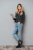 Girl standing and holding tablet computer over grey background royalty free stock photography
