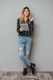 Girl standing and holding tablet computer over grey background stock photography
