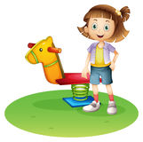 A girl standing beside a horse spring toy Royalty Free Stock Photo
