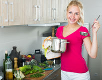 Girl standing at kitchen and cooking soup Royalty Free Stock Photography