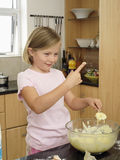 Girl (6-8) standing in kitchen, dipping finger into bowl of cake mix, holding spoon, smiling Royalty Free Stock Photos