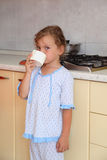 Girl standing in kitchen and drinking milk royalty free stock photo