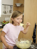 Girl (6-8) standing in kitchen, eating cake mix from bowl, holding spoon, smiling, portrait Royalty Free Stock Photo
