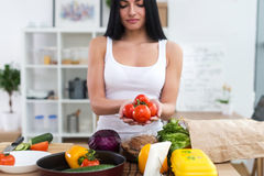 Girl standing at kitchen holding red tomato bunch in her hands. Housewife taking fresh ingredients for vegetable salad. Royalty Free Stock Photography