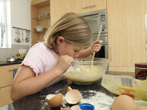 Girl (6-8) standing in kitchen, mixing flour, eggs and milk in bowl with wooden spoon, side view Royalty Free Stock Photo