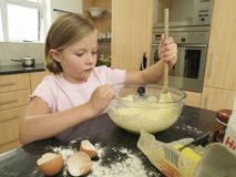 Girl (6-8) standing in kitchen, mixing flour, eggs and milk in glass bowl with wooden spoon Royalty Free Stock Images
