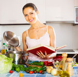 Girl standing at kitchen with vegetables Stock Images