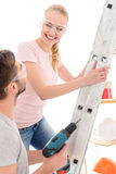 Girl standing on ladder near guy holding drill Stock Photo