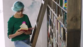 Girl standing on ladder searching book in library stock footage