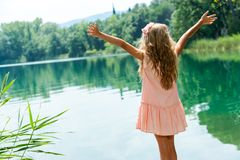 Girl standing at lakeside with open arms. Stock Photos