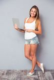 Girl standing with laptop and looking at camera Stock Photography
