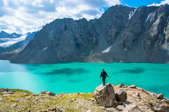 Girl standing on a large rock on a background of a mountain lake Stock Image