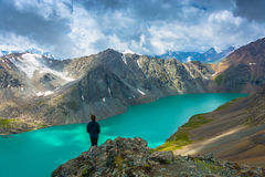 Girl standing on a large rock on a background of a mountain lake Stock Images