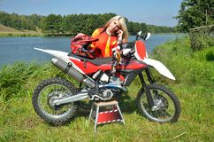 Girl is standing leaned on the motorbike Stock Images