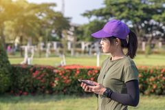 Girl standing listening to music in the park. royalty free stock image