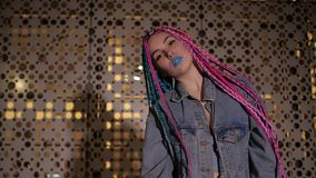 Girl is standing looking at camera. Blue and pink haired girl with blue lips is standing by the wall outside looking at camera stock video