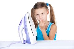 Girl standing and looking at iron at home. Royalty Free Stock Photo