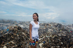Girl standing and looking a side sad with  trash around at garbage dump. Maldives Stock Photos