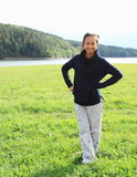 Girl standing on meadow by lake Stock Photo