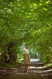 Girl standing in the middle of the green alley summer day Royalty Free Stock Photo