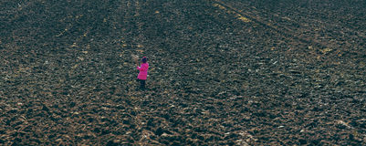 Girl standing in the midst of plowed fields Royalty Free Stock Images
