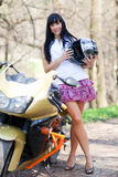 Girl standing beside a motorcycle. Biker Girl standing beside a motorcycle and holding a helmet. beautiful woman standing next to a motorcycle Outdoors. girl in Stock Photography