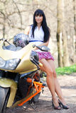 Girl standing beside a motorcycle. Biker Girl standing beside a motorcycle and holding a helmet. beautiful woman standing next to a motorcycle Outdoors. girl in Stock Photo