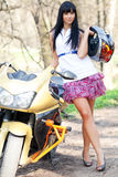 Girl standing beside a motorcycle. Biker Girl standing beside a motorcycle and holding a helmet. beautiful woman standing next to a motorcycle Outdoors. girl in Royalty Free Stock Photos