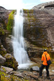 Girl standing near the beautiful waterfall and and looking at it Royalty Free Stock Photos