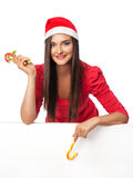 Girl standing near a big white  board and  holds  a candy cane Stock Images