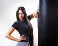 Girl standing near body hitting pear. Royalty Free Stock Image
