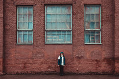 Girl standing near a brick wall Stock Photos