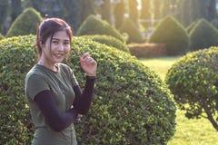 Girl standing near a bush in a park. stock photo
