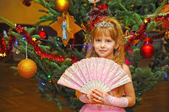 Girl standing near decorated Christmas tree  with the crown on the head Royalty Free Stock Photos