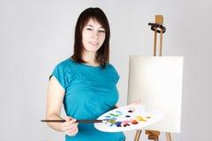 Girl standing near easel, holding palette Stock Images