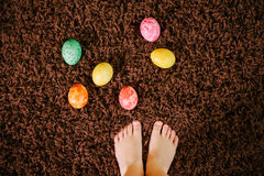 Girl standing near Easter eggs. top view, flat lay. feet Stock Images