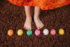 Girl standing near Easter eggs. top view, flat lay.feet. Stock Photo