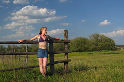 The girl standing near the fence. One girl stands in the summer on the nature Royalty Free Stock Image
