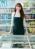 Girl standing near fridge with frozen goods Royalty Free Stock Photos