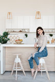 Girl standing near the kitchen table in a high chair. Bright, white kitchen. Happy smiling girl in the kitchen. Girl royalty free stock images
