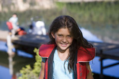 Girl (7-9) standing near lake jetty, wearing red life jacket, smiling, front view, portrait Stock Photo