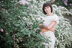 Girl standing near lilacs. Beautiful young woman in a white dress standing among white blossoms and lilacs Stock Images