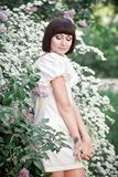 Girl standing near lilacs. Beautiful young woman in a white dress standing among white blossoms and lilacs Royalty Free Stock Image