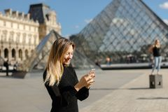 Free Girl Standing Near Louvre And Glass Pyramind In Black Dress In Paris, Texting By Smartphone. Stock Photos - 117998033